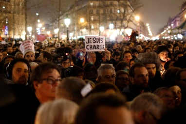 "A man holds a placard reading ""I am Charlie"" as he attends a vigil to pay tribute to the victims of a shooting by gunmen at the offices of weekly satirical magazine Charlie Hebdo in Paris at Republique square"